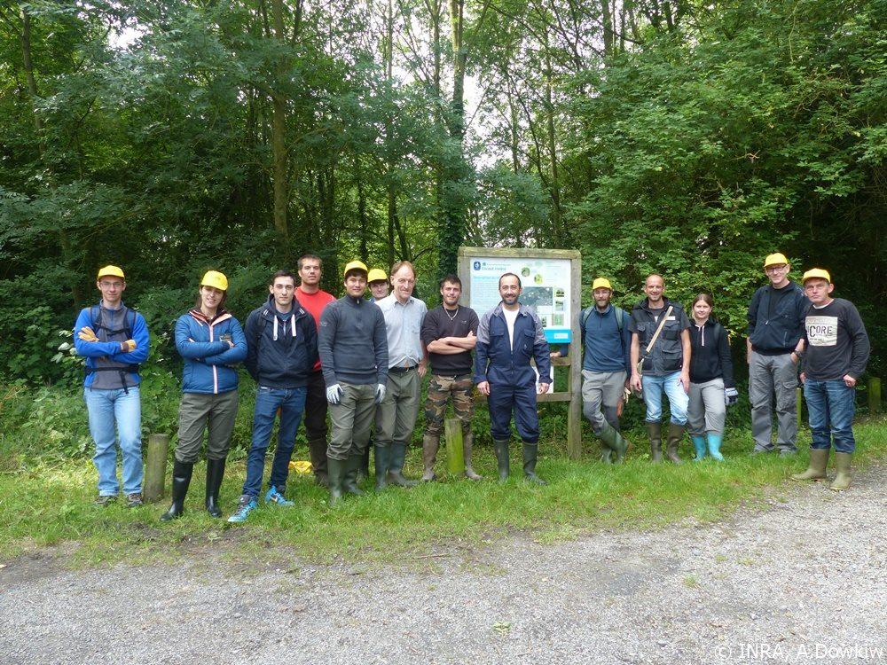 Les bénévoles posant devant le panneau d'accueil de la RNR de l'Escaut rivière - Photo : © INRA, Arnaud Dowkiw